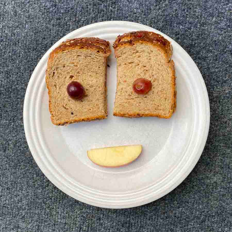 Peanut butter sandwich, grapes and apple slices on a plate are a fun and healthy kids' snack!