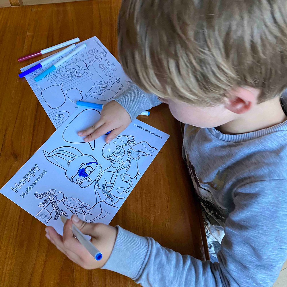 A left-handed child is coloring in a coloring page of bunny rabbits with a blue marker.