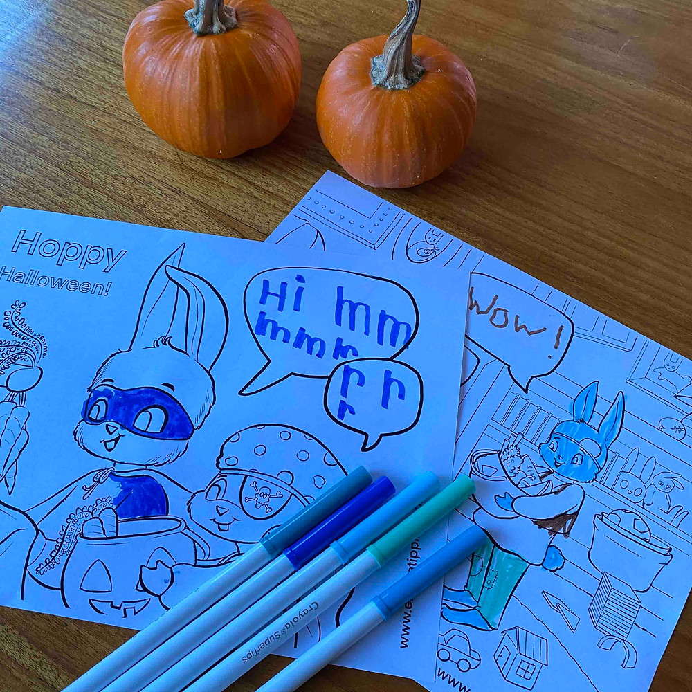 Blue and green markers rest on top of Halloween coloring pages beside some cute pumpkins