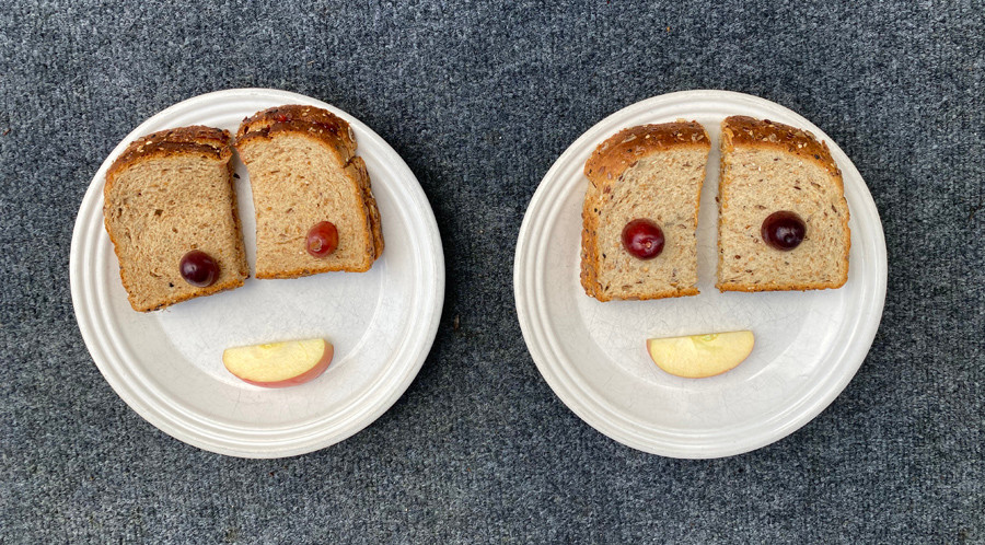Peanut butter sandwiches with grapes and apple slices are places on plates in the form of faces.