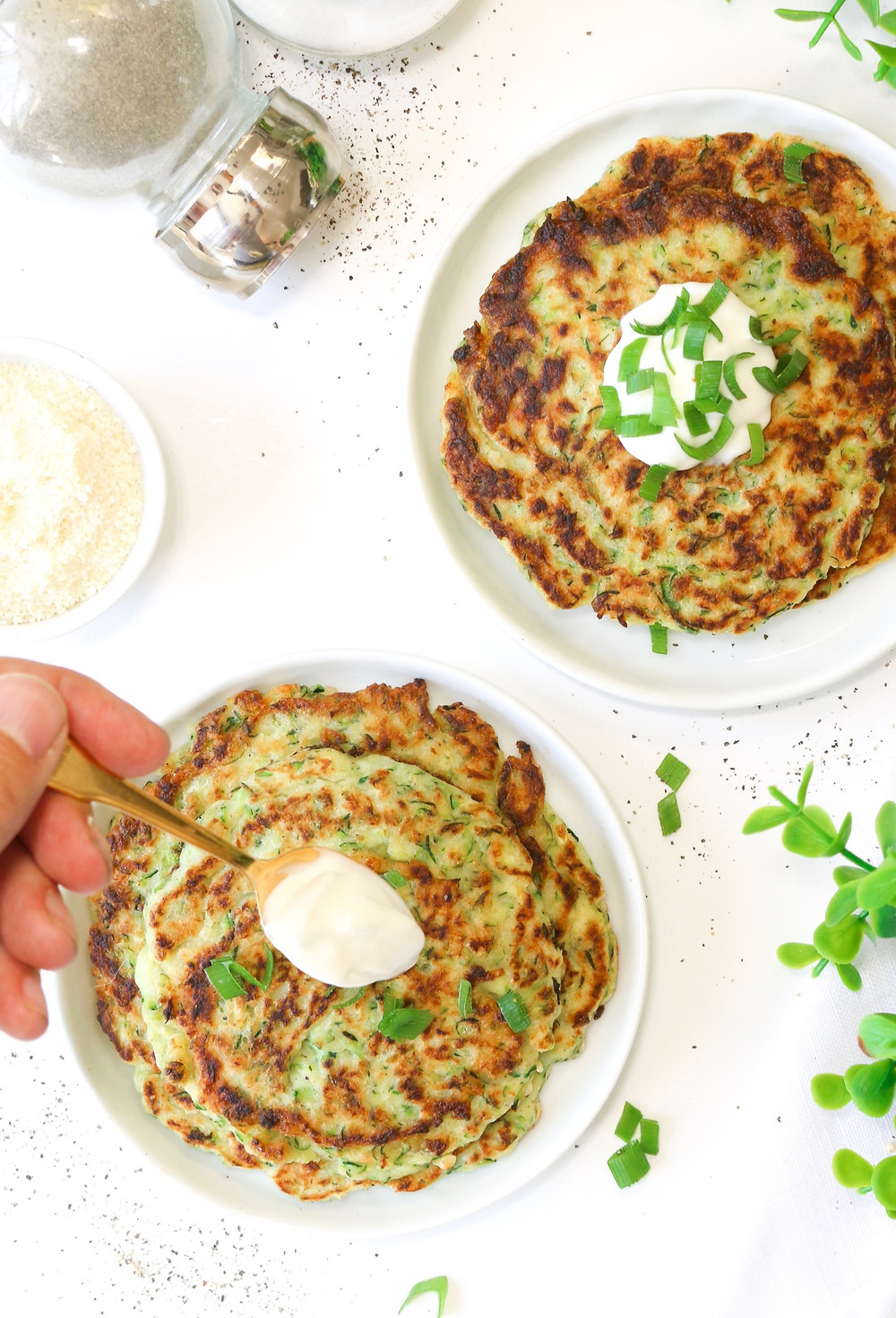 Pan fried gluten-free zucchini fritter with sour cream and green onions