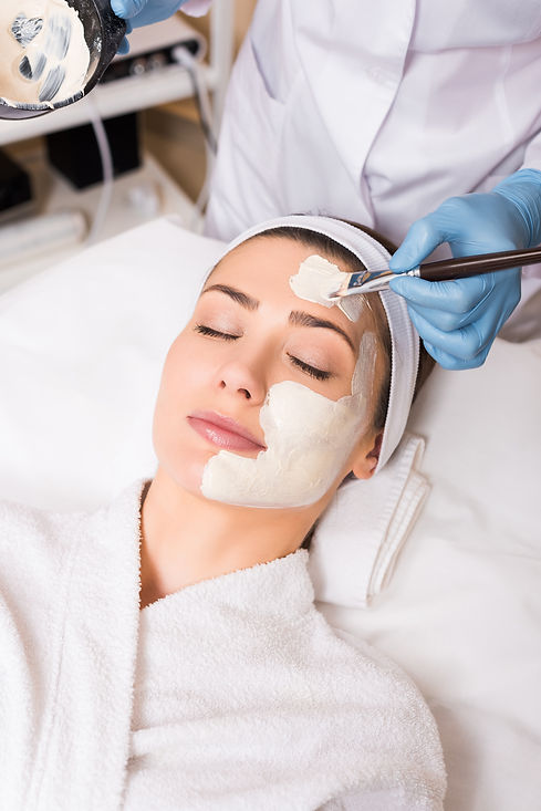 beautician-applying-cosmetic-mask-on-woman-face-wi-LBG5F5T.jpg