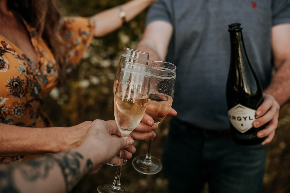 Photographer having champagne with a couple during their engagement session