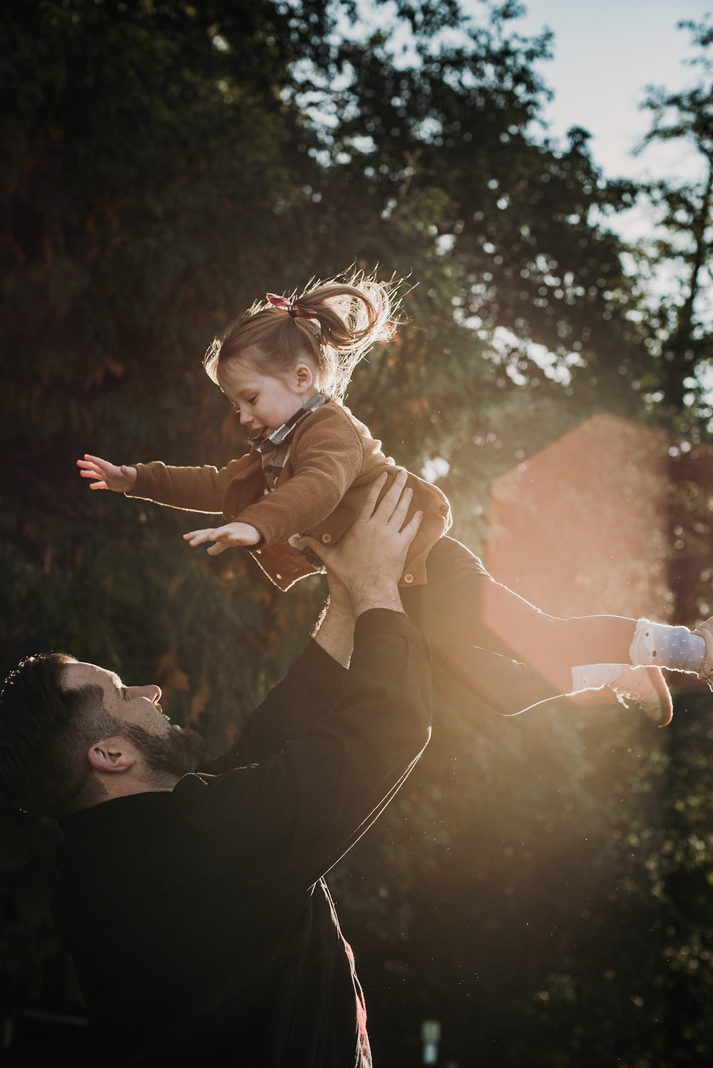 Dad playfully throwing daughter in the air at Tolmie State Park in Olympia, WA. Their family pictures were captured by Cherish Harper at Cherish Shanell Photography