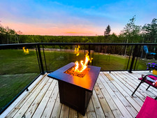 Both domes offer a stunning view of the wooded skyline which can be seen while relaxing next to the propane fire table.