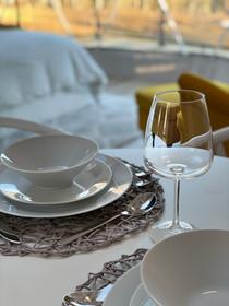 Dinnerware, glassware, and utensils are provided.
