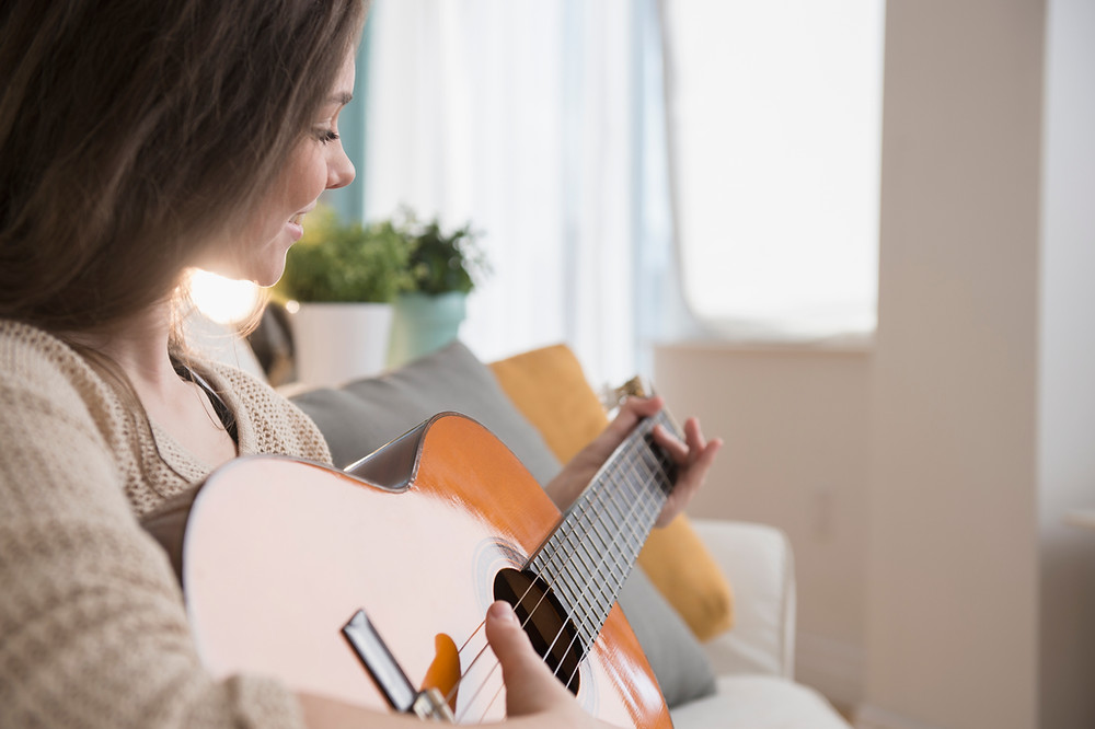 woman playing guitar relaxing