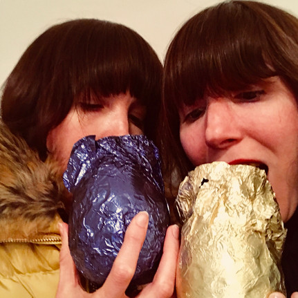 Two selfish women put chocolate between their teeth....