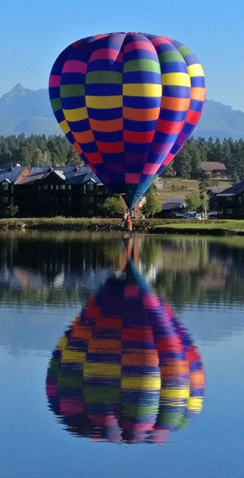 Hot air balloon hovering over a lake, its reflection in full view