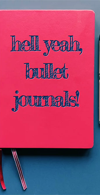 """Red bullet journal and pen, with the text """"hell yeah, bullet journals!"""" inscribed on the cover of the journal"""