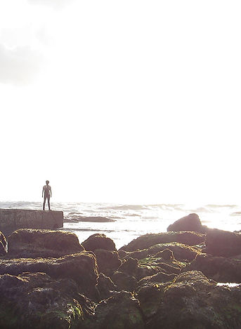Person in silhouette standing at the edge of the open sea, looking into a bright sky