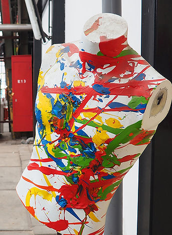 Mannequin torso splattered in various bright colors of paint