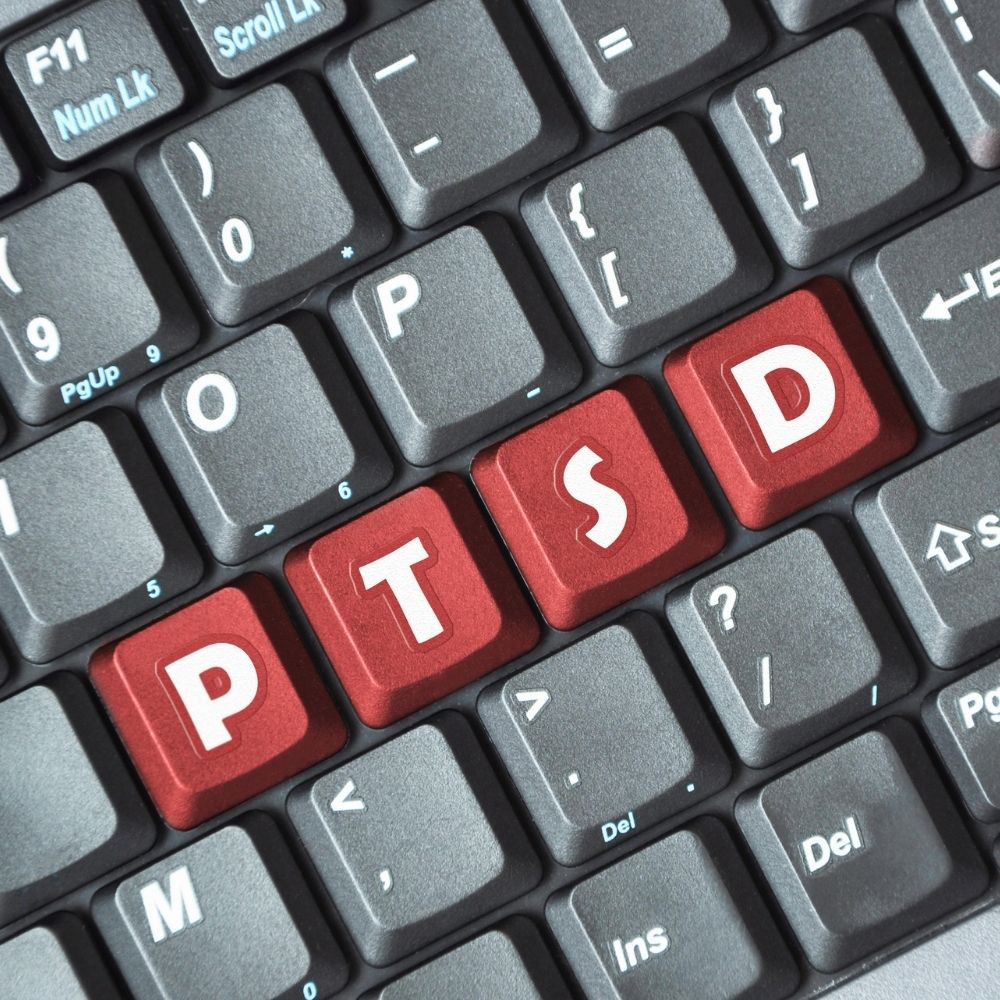 The letters PTSD are spelled and highlighted on a keyboard, symbolizing online PTSD tests.