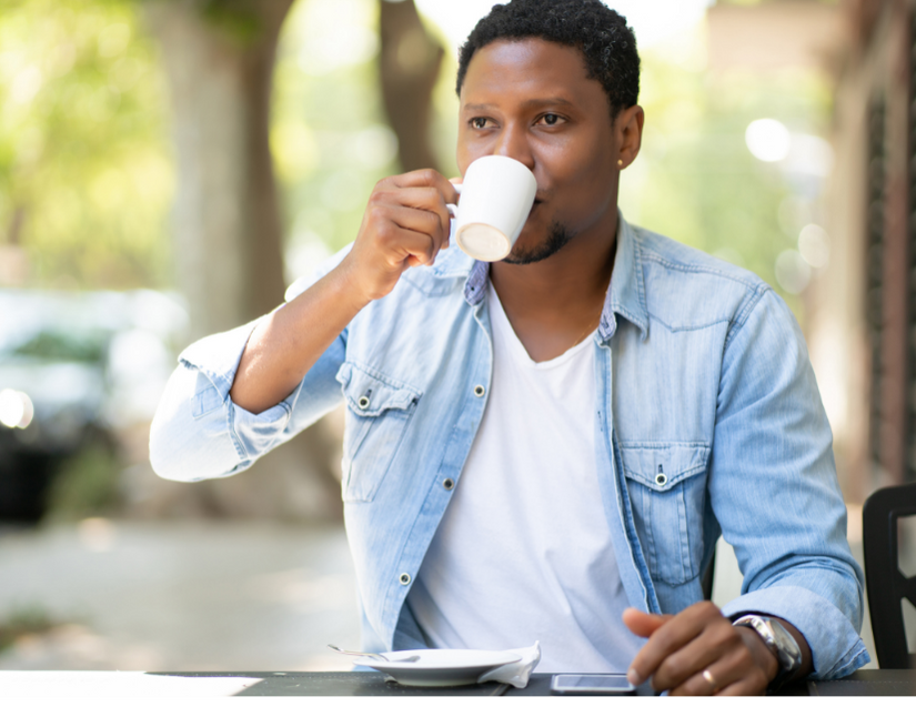A man sips coffee, one way to activate the senses for grounding.