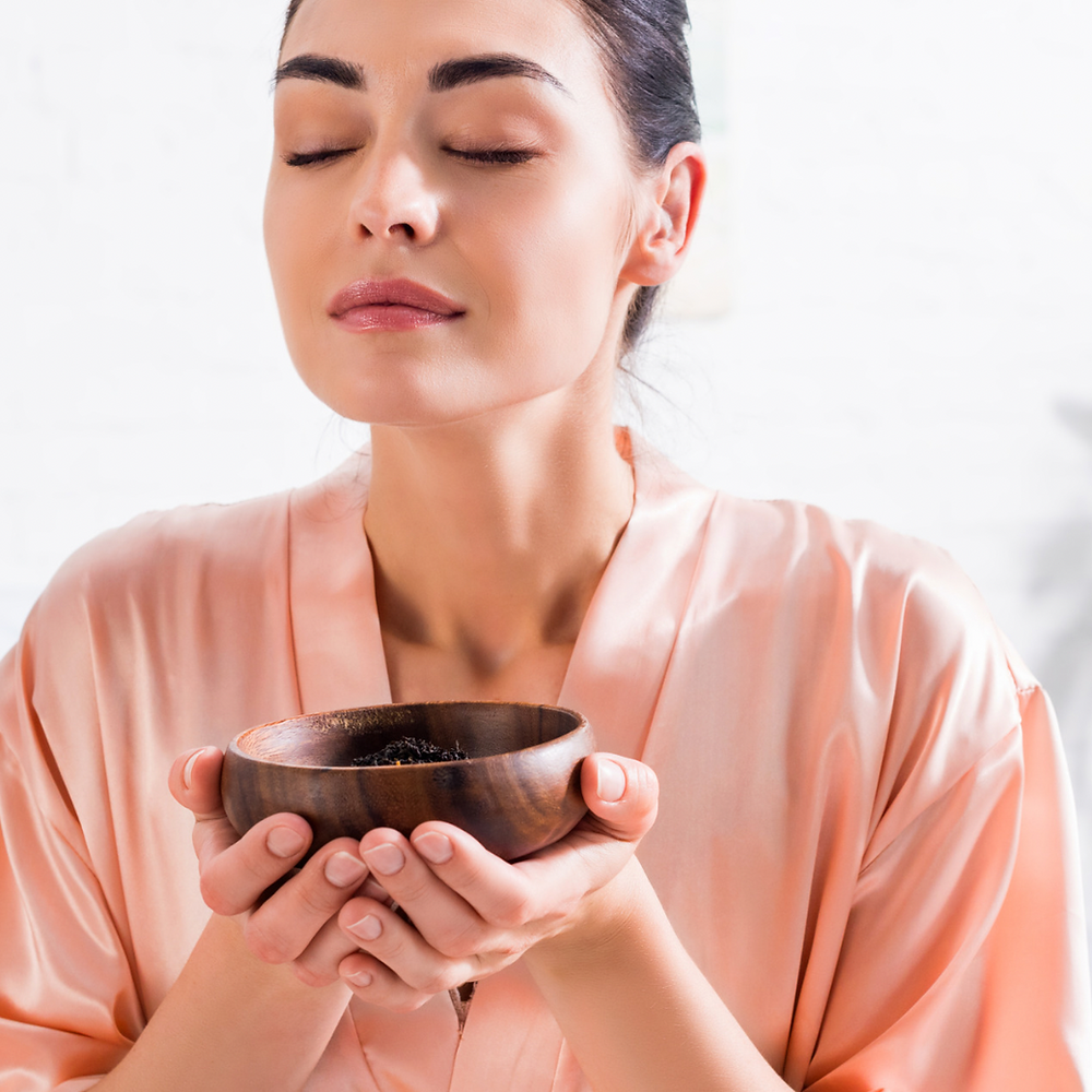 A woman smells scents from a wooden bowl. Aromatherapy is one grounding technique.