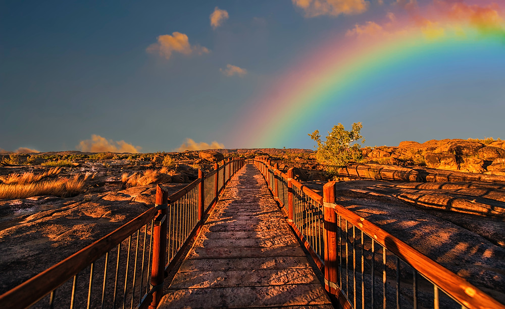 A rainbow meets the end of a trail in the distance.