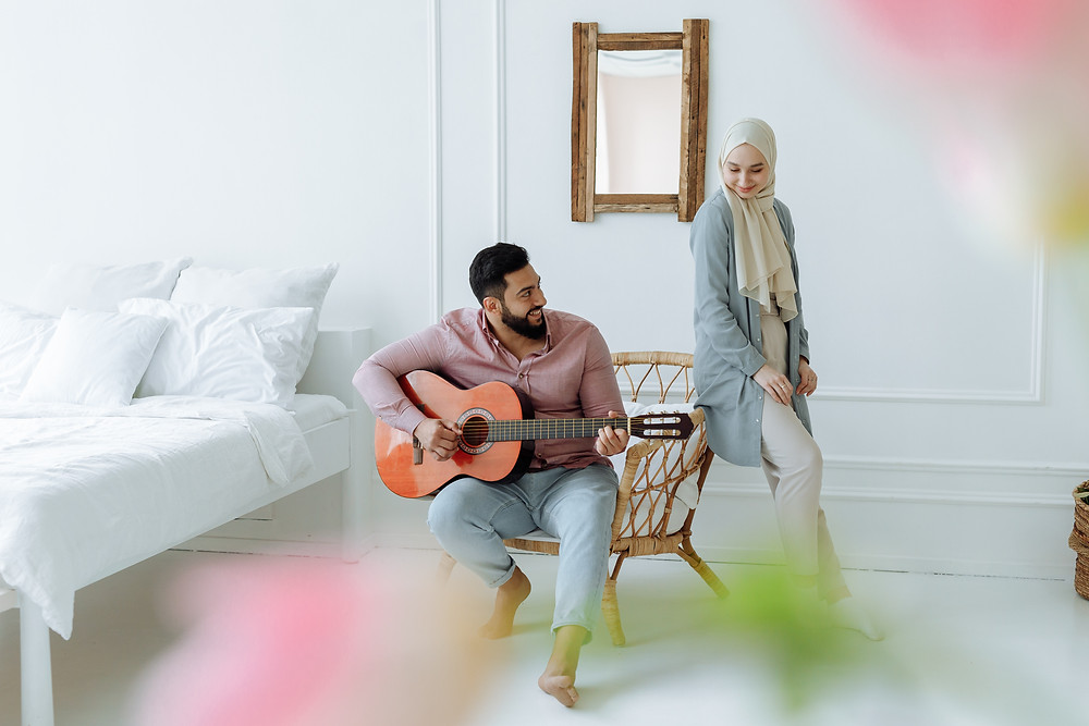 A woman watches a man play guitar, demonstrating music as a form of self-care.