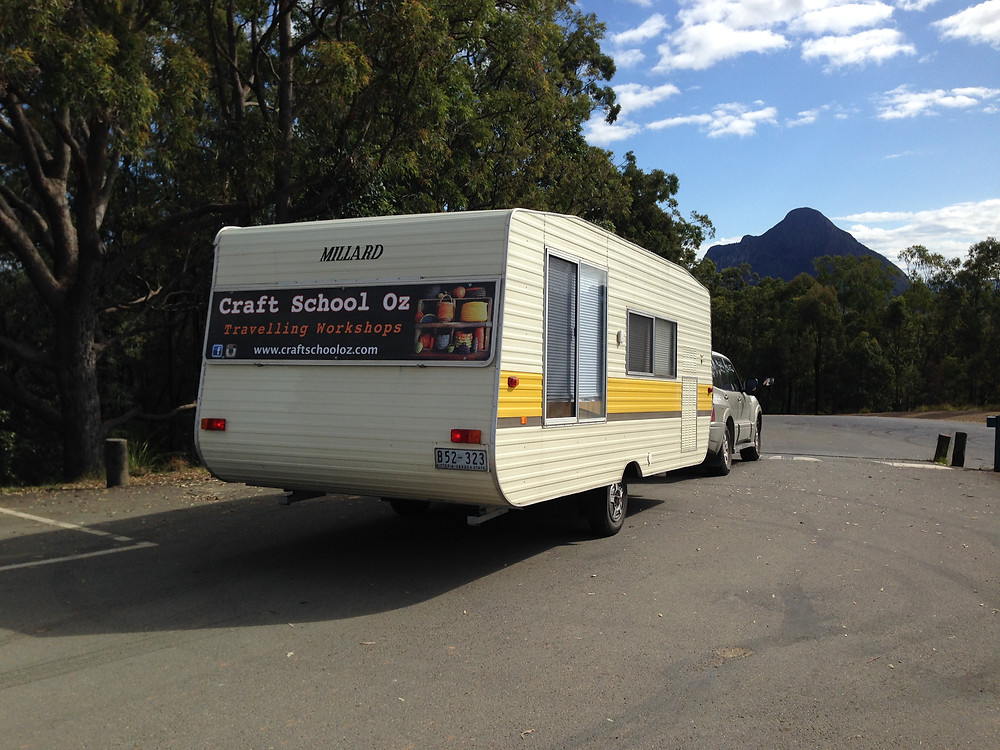 This is an image of a white and yellow vintage 1980's caravan. It is white with a yellow stripe and has Craft School Oz written on it.