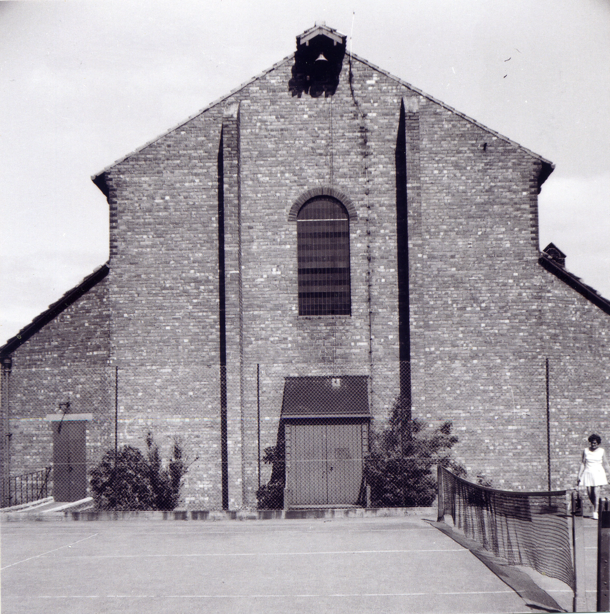The temporary west end of the church and the adjoining tennis court. The building was completed in t