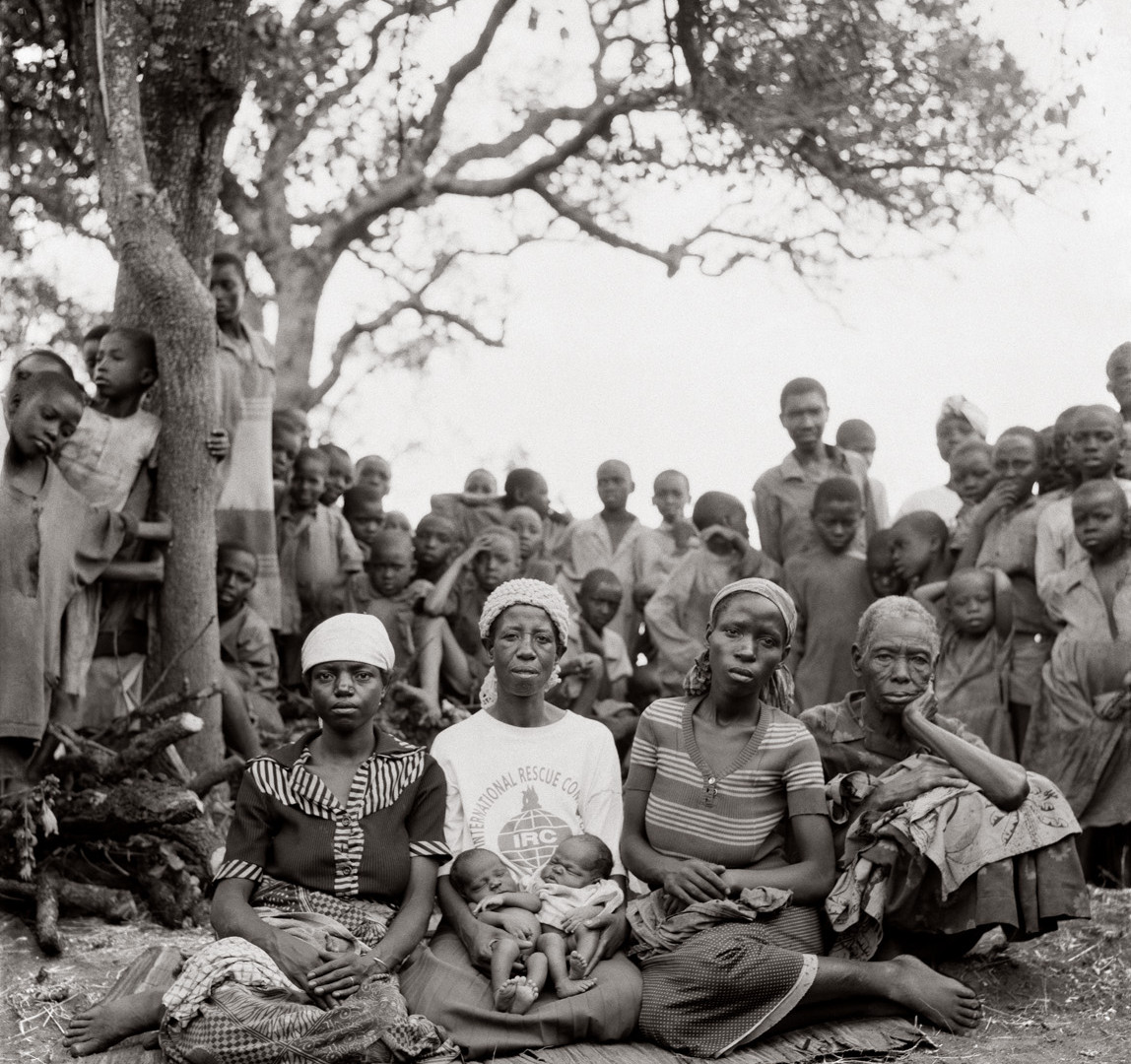 "Fazal Sheikh, Traditional birthing attendant Nyirabahire Esteri, holding newborns Nsabimana (""I beg something from God"") and Mukanzabonimpa (""God will grant me, but I do not know when""), flanked by mothers Kanyange, Mukabatazi, and Mukabatazi's mother, 1994"