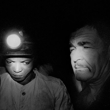 David Goldblatt, Shiftboss with 'his piccanin,' underground at Randfontein Estates Gold Mine. For the shiftboss the young man carried measuring instruments, a bottle of tea and a 'pneumo' jacket; for me - at the shiftboss's insistence and over my objections - he carried my tripod. Randfontein, Transvaal (Gauteng). , 1965