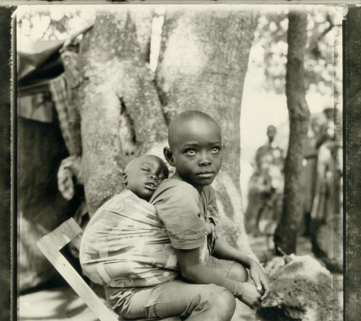 "Fazal Sheikh, Wezemana (""God is great"") with her sleeping brother Mitonze, Rwandan refugee camp, Lumasi, Tanzania, 1994"