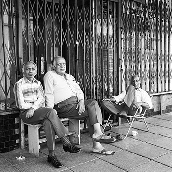 David Goldblatt, Ebrahim Moolla and Shaikjee and Habib Sakoor listen to the cricket commentary on a Saturday afternoon on 14th Street, Fietas, before its destruction under the Group Areas Act. , 1976