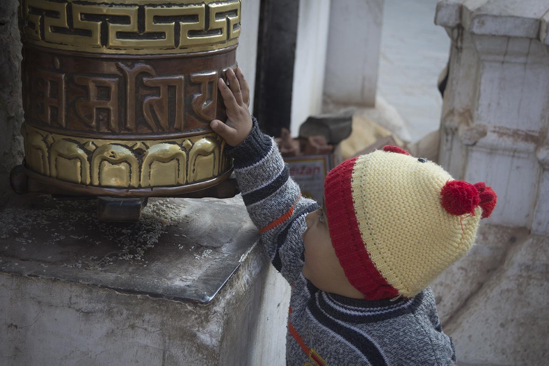 Niño girando molino de oraciones