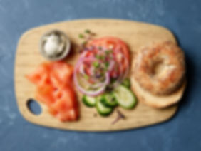 Everything Bagel & Smoked Salmon with tomato, cucumber, red onion, capers, and cream cheese on a cutting board with a blue background
