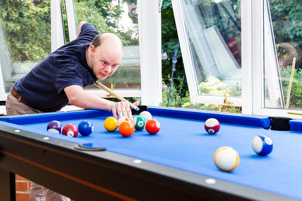 A resident of the Anthony Toby Homes Trust playing pool