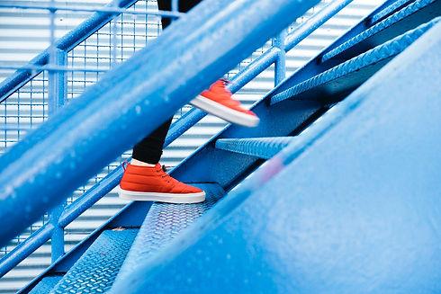 Man walking up stairs in orange sneakers