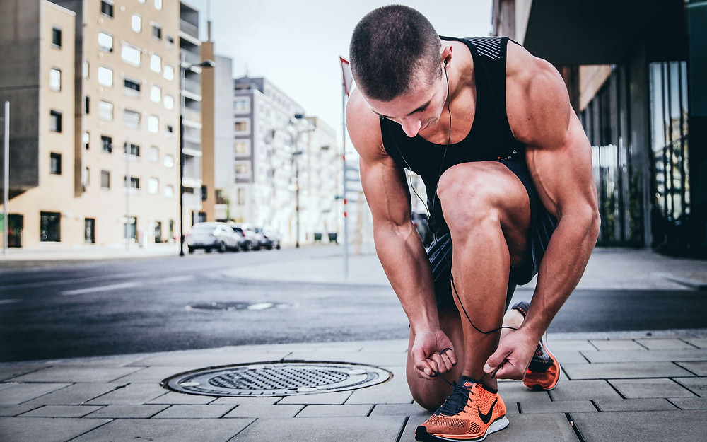 A fit man tying his shoe lace