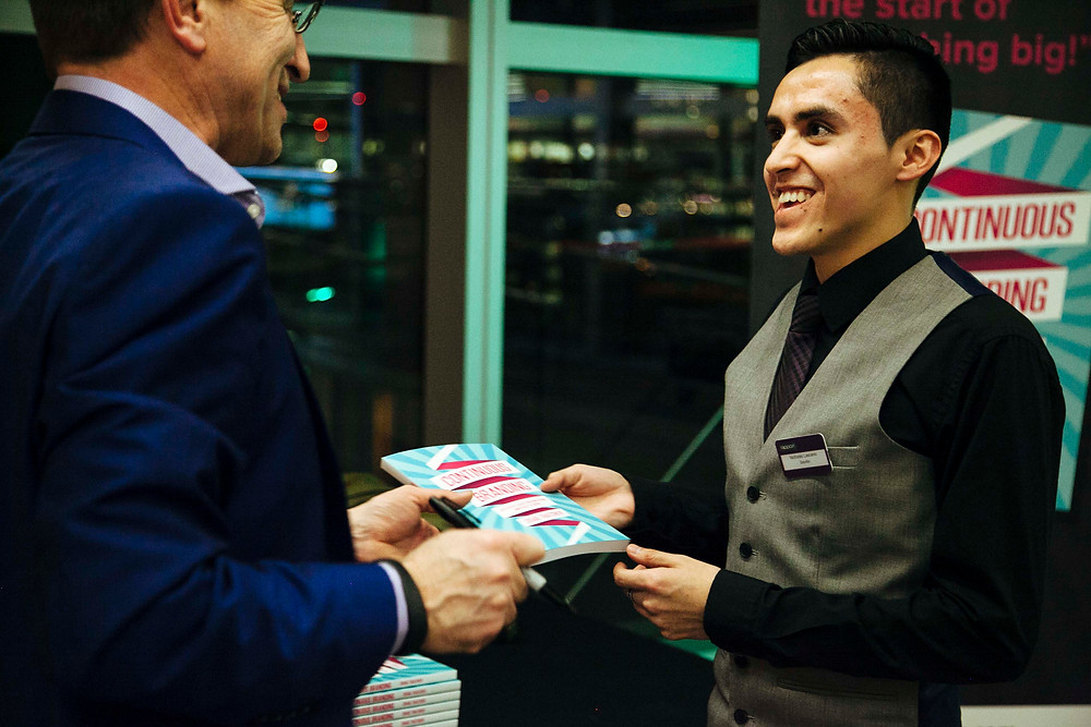 Craig handing a copy of Continuous Branding to an attendee