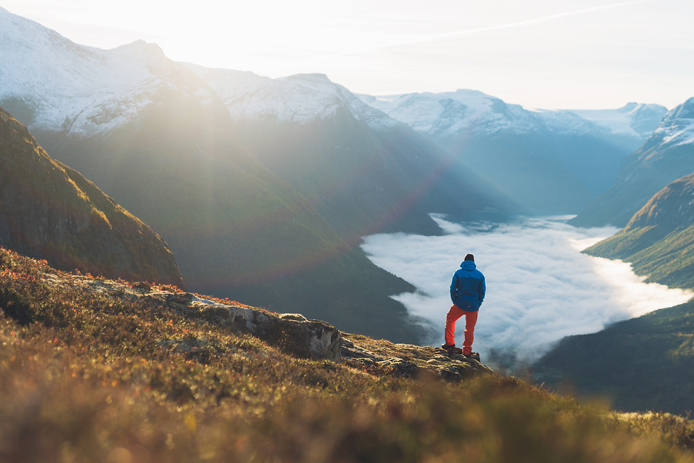 view over norwegian mountains and a hiker out on the edge