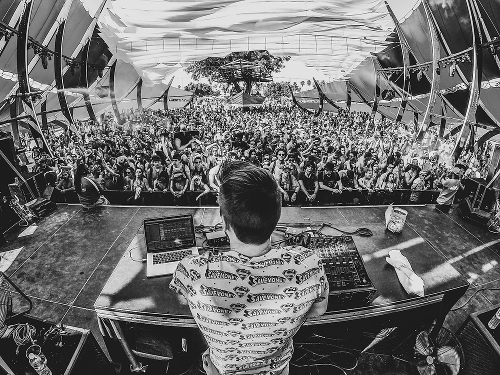 DJ playing a set on stage for large crowd