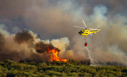Helicopter with bambi bucket dumping wat