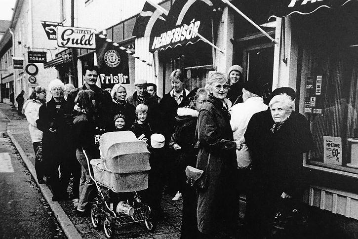 Vadstena frisörsalong. folk väntar utanför salongen i rådhustorget i vastena för att klippa sitt hår. 60 års jubileum i vadstena