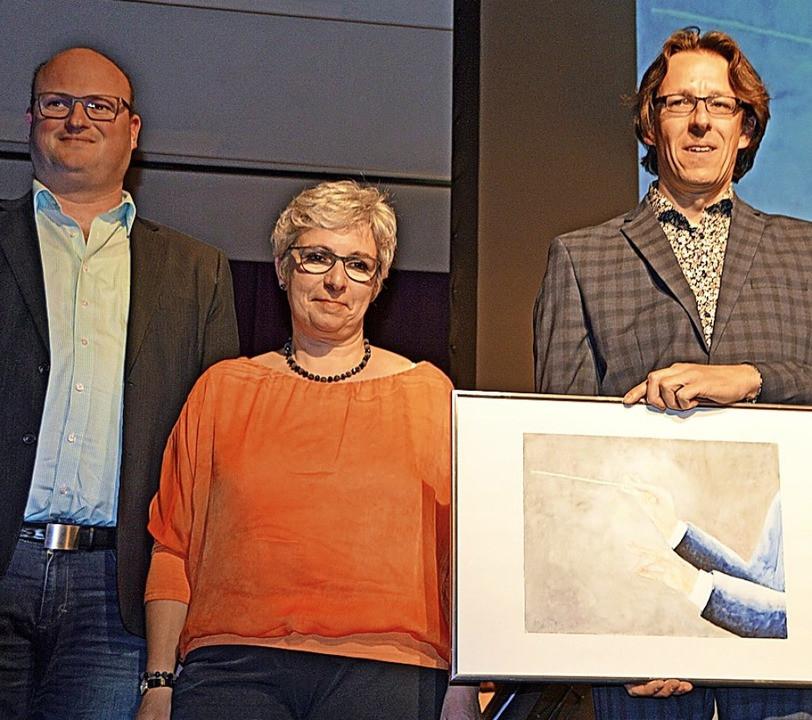 Für 30 Jahre Dirigententätigkeit bekam Gregor Heinrich (rechts) von Clemens Zeissler die Goldene Dirigentennadel, Susanne Gärtner überreichte ein von Andrea Saier gemaltes Bild. Foto: Gerhard Lück