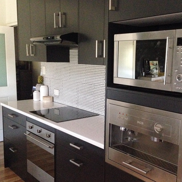 After - sleek black and white with penny round tiles splashback