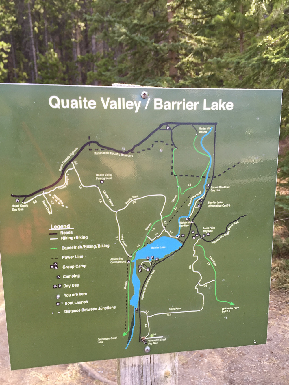 Green sign that stands in front of the trailhead