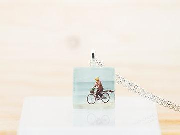 Dame à bicyclette, pendentif