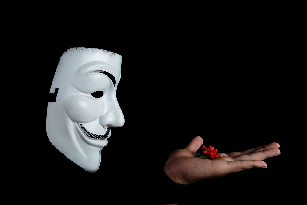 Black background, anonymous mask on person