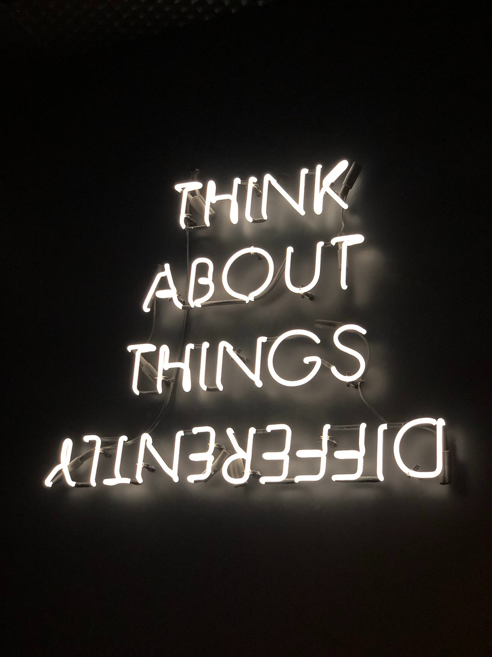 Black background, white neon sign that says Think about thinkgs differently
