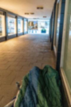 Dieses Bild zeigt einen Durchgang in der Knochenhauerstraße, in dem ein Obdachloser sich ausgebreitet hat.