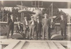 0225 Eight men in front of plane