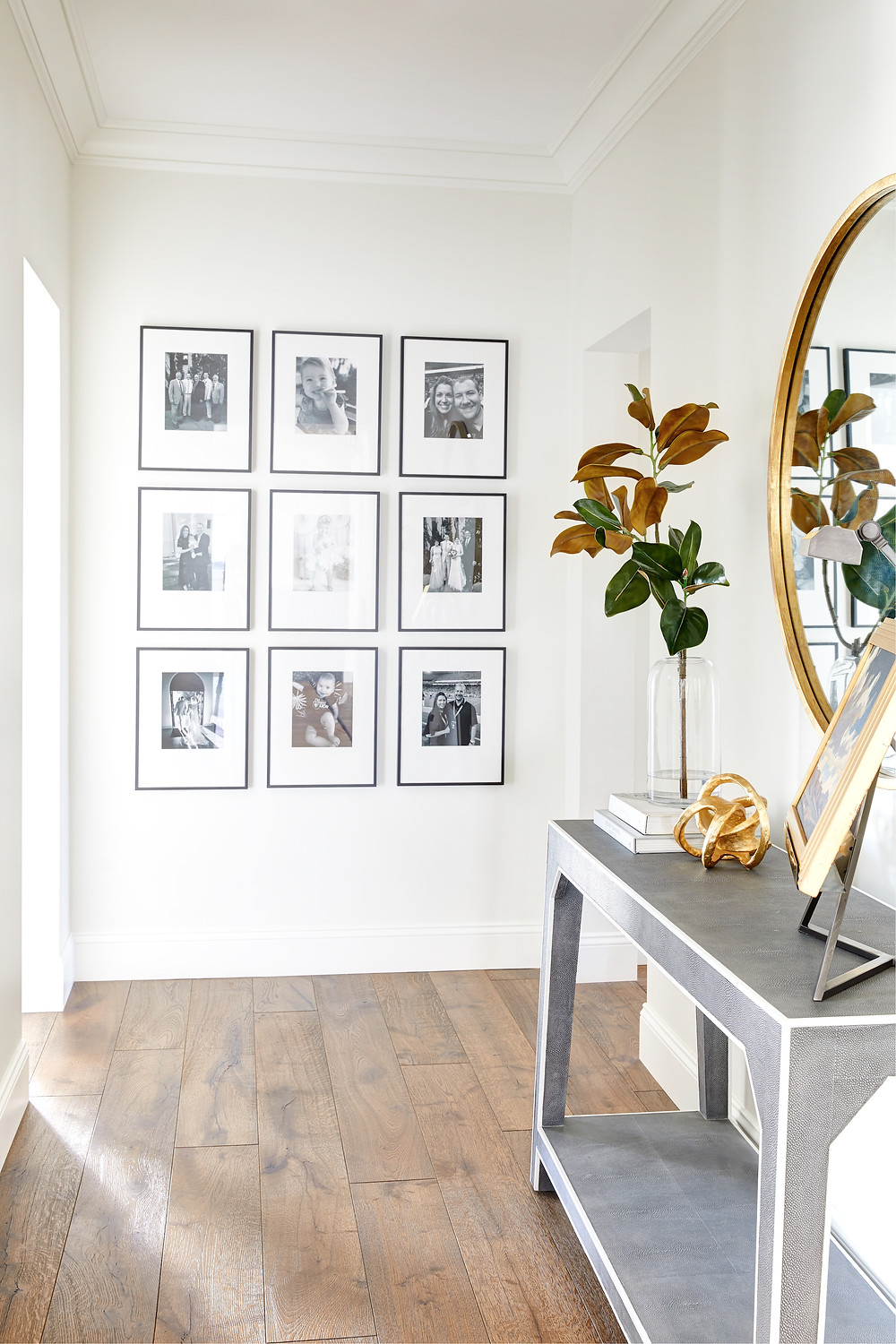 Bright and airy transitional hallway design with black and white photo gallery wall and styled console table. Click through for the 7th Avenue Project reveal by Phoenix based interior designer, Lexi Westergard Design.
