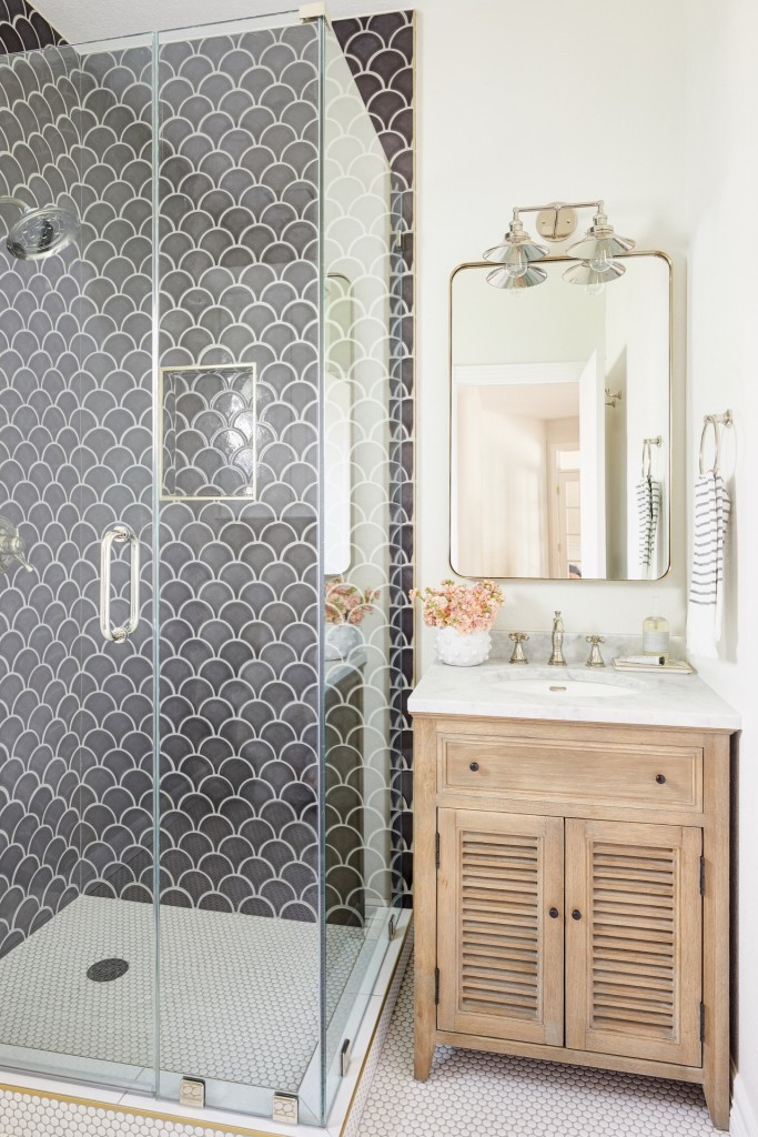 The difference between a full furnishing project and a remodel or new construction project. Blue fish scale handmade clay tile shower with natural wood custom vanity and brass accent bathroom designed by Lexi Westergard Design.