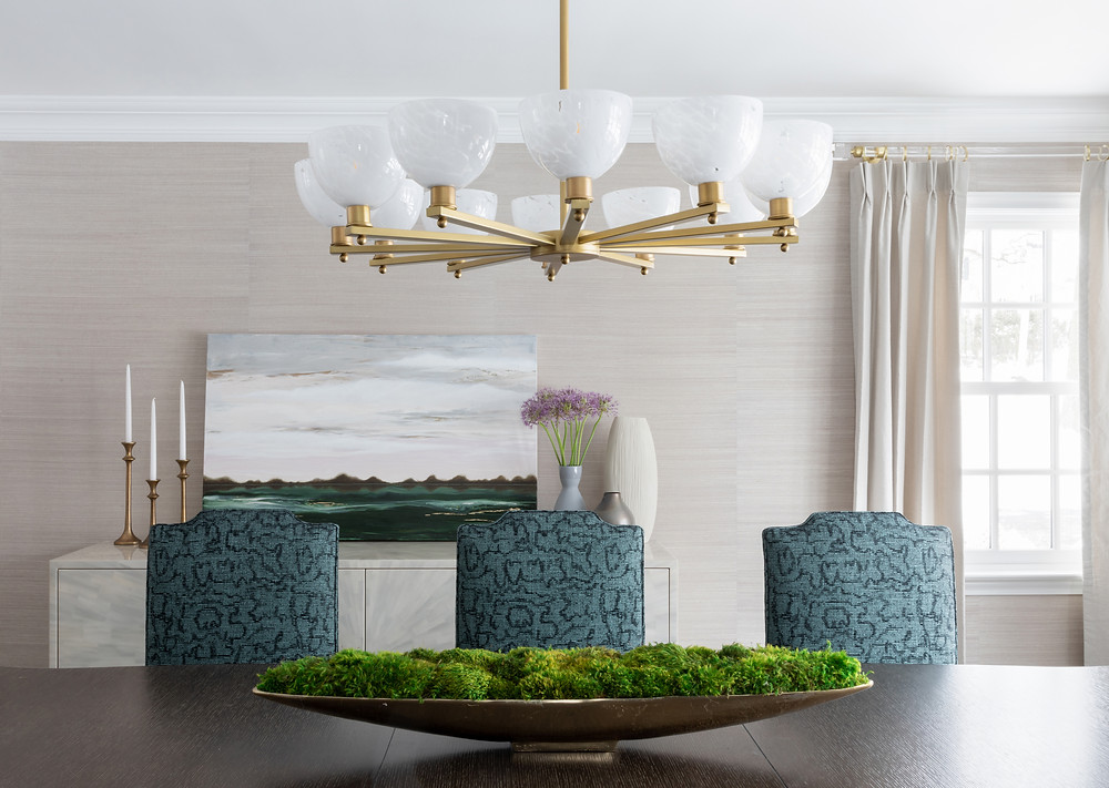 dining space with grasscloth wallpaper and brass chandelier