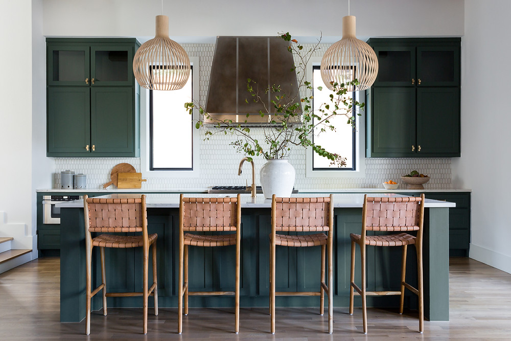 kitchen with green cabinets and woven leather bar stools