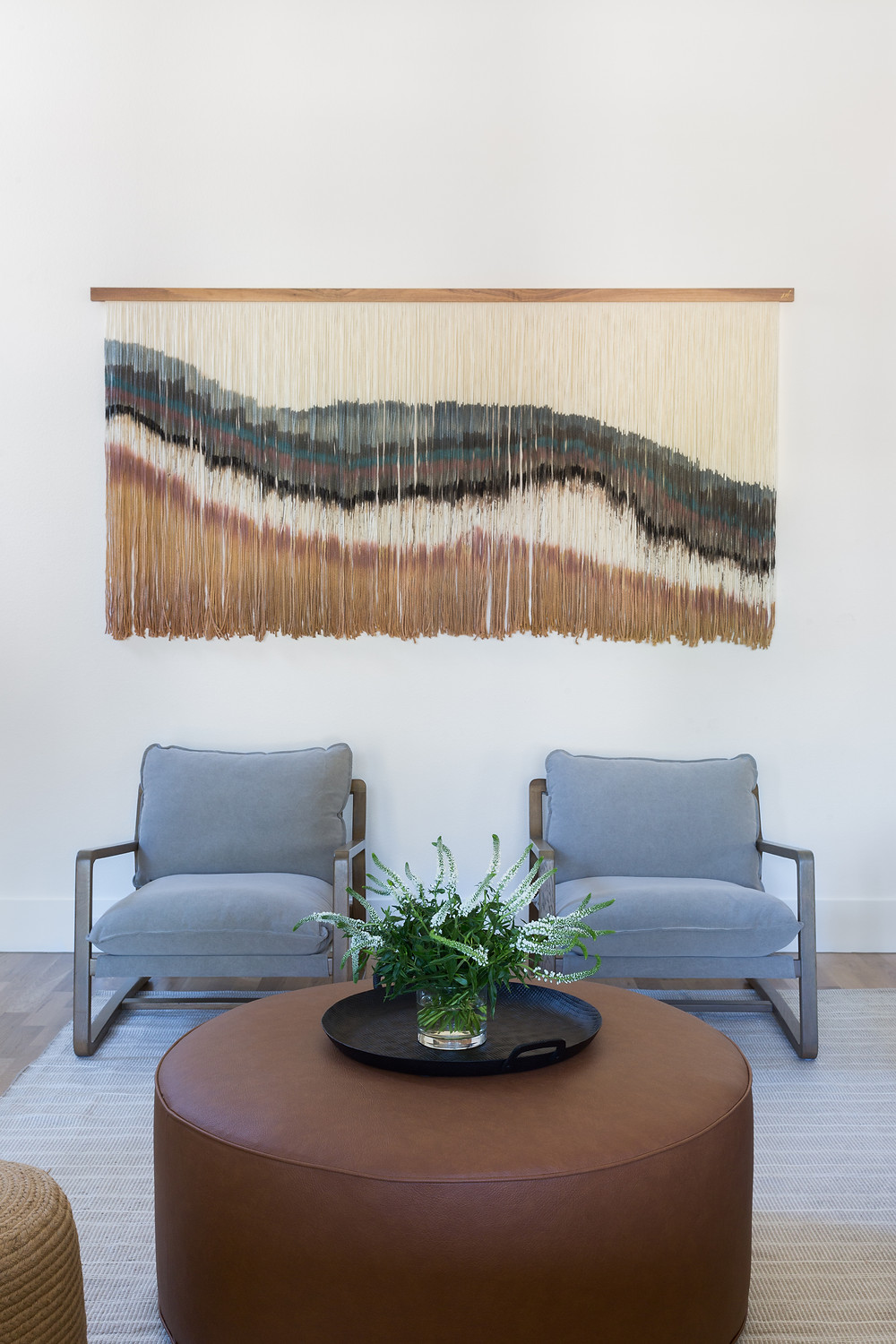 two chairs with woven art piece